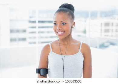 Smiling attractive woman in sportswear listening to music in bright room at home