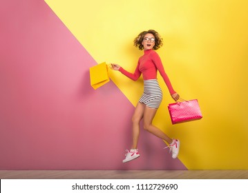 smiling attractive woman, stylish colorful outfit jumping with shopping bags, happy, pink yellow background, polo neck, striped mini skirt, sale, discount, shopaholic, fashion summer trend, emotional