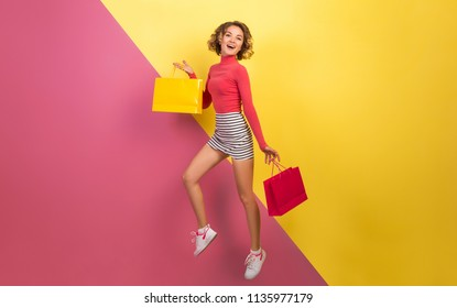 smiling attractive woman in stylish colorful outfit jumping with shopping bags, happy, pink yellow background, polo neck, striped mini skirt, sale, discount, shopaholic, fashion summer trend, emotiona