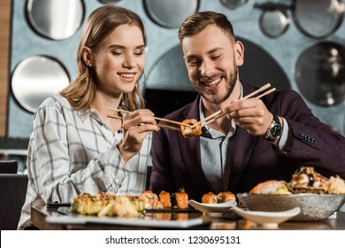 Smiling attractive young adult couple eating sushi together in restaurant