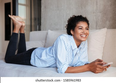 Smiling attractive young african woman wearing shirt relaxing on a couch at home, using mobile phone while laying