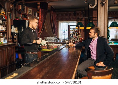 Smiling attractive young barman wiping glasses and talking to man in bar