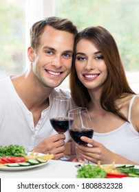 Smiling attractive young couple drinking red wine, at home. Portrait image of caucasian models with redwine glasses in love concept. Happy man and woman posing together indoors. 14 february, valentine