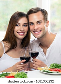 Smiling attractive young couple drinking red wine, at home. Portrait of caucasian models with redwine glasses in love concept. Happy man and woman posing together indoors.