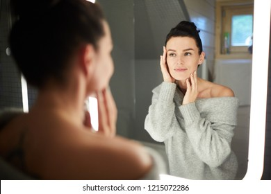 Smiling attractive young lady in sweater looking into mirror and touching face while applying cream on cleaned face in bathroom