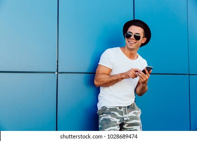 Smiling attractive young man with cell phone, looking away. Dressed in t-shirt, shorts, in hat and sunglasses. Outdoors. Copy space.