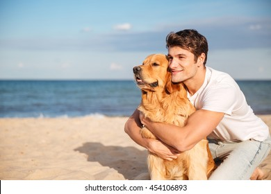 Smiling attractive young man hugging his dog on the beach in summer
