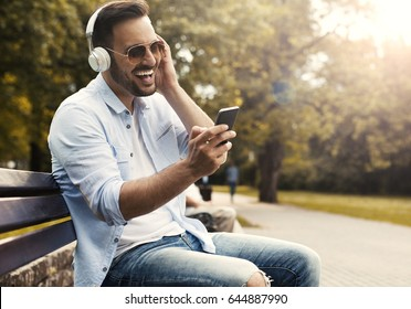 Smiling attractive young man using headphones and singing at the public park