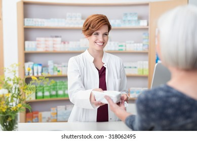 Smiling attractive young redhead pharmacist handing over prescribed medicines to an elderly female patient, view over the clients shoulder of the pharmacist