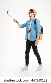 Smiling attractive young tourist with backpack walking and using mobile phone on selphie stick over white background