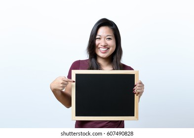 Smiling attractive young woman pointing to a blank blackboard with copy space for your text that she is holding in front of her chest