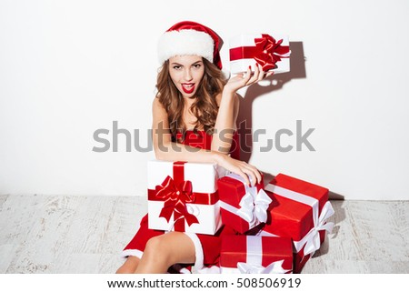 138fc536f1268 Smiling attractive young woman in santa claus costume sitting and holding  present box isolated on the