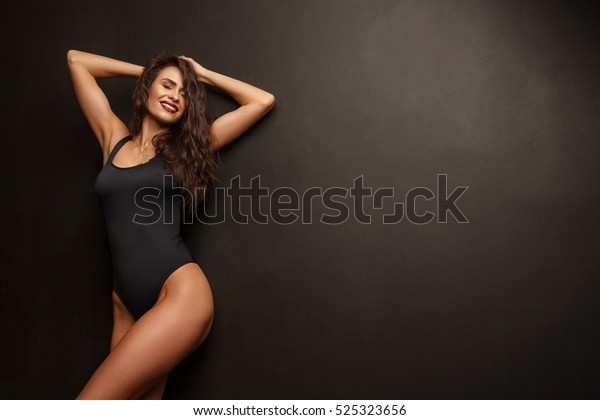 Smiling attractive young woman with sexy shapely forms, loose wavy hair, red lipstick and slim body is posing in the black underwear, studio photoshoot, dark background
