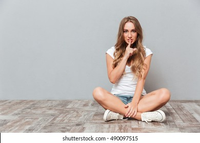 d40df7f26ced Smiling attractive young woman showing silence gesture while sitting on the  floor over gray background