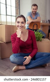 Smiling attractive young woman sitting cross legged on the floor in front of packing cases watched by her husband in the background as they pack up to move home