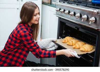 Smiling attractive young woman taking tray with croissants from oven on the kitchen at home