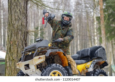 Smiling atv rider with paintball gun on his quad bike
