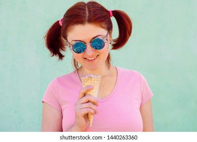 Smiling audacious young woman with pigtails hairstyle holds ice-cream in waffle cone, it reflects in round sunglasses, shabby turquoise wall in background. Summer heat, quick meal, urban style concept