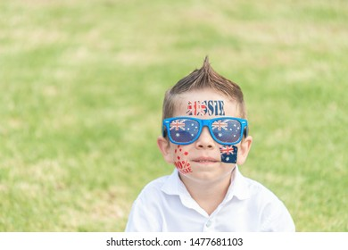 Smiling Australian boy with sunglasses sitting on lawn during Australia Day celebration