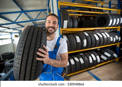 smiling auto mechanic carrying tire in tire store