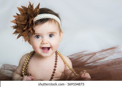 Smiling baby ballerina in brown tutu with a pearl necklace