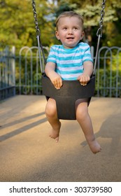 Smiling baby boy having fun on the swing in the city park