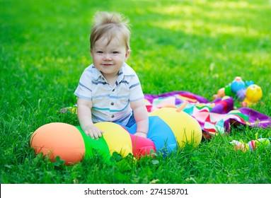 Smiling baby boy on background of toys and grass in park