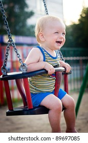 Smiling  baby boy sitting in a swing