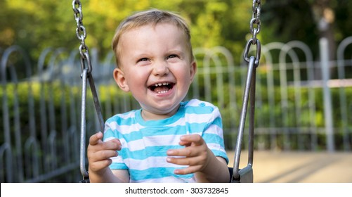 Smiling baby boy swinging in the city park during summer