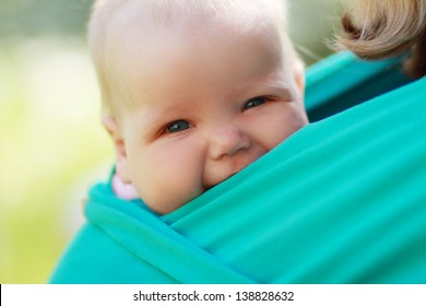 Smiling baby closed to mom in sling outdoor