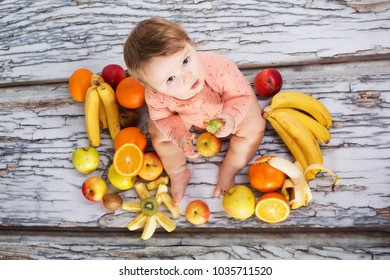 Smiling baby eating banana and many kinds of fruit and bowl with yoghurt