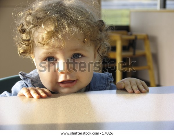 smiling baby in a fast food restaurant ready to eat