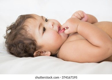Smiling baby with finger in mouth on the bed