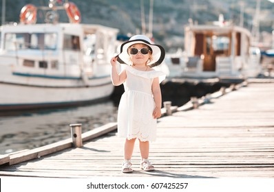 Smiling baby girl 1-2 year old wearing white summer dress and hat walking on wooden pier at sea shore outdoors. Looking at camera. Childhood.