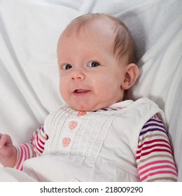 Smiling Baby Girl Looking at Camera and Sitting on White Blanket