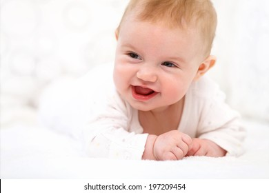 Smiling Baby Girl are Lying in the Bed