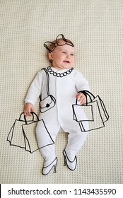 Smiling baby girl lying on bed with shopping bags