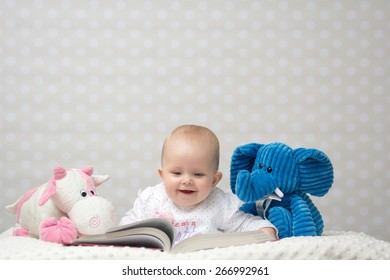 Smiling baby girl reading a book with little toy friends