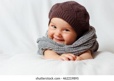 Smiling baby girl in scarf and beret
