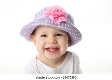 db30e16f407 Smiling baby girl showing teeth wearing a purple polka dot hat with pink  flower isolated on