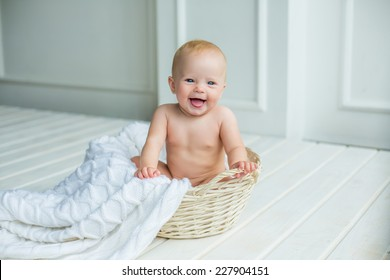 smiling baby girl sitting in basket with white blanket in white interrior