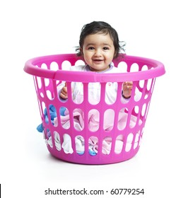 Smiling Baby Girl Sitting in the Laundry Basket on White Background