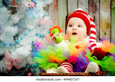 Smiling baby girl sitting under a blue tree in a striped hat red and white color. The concept of a new year. On a Christmas card.