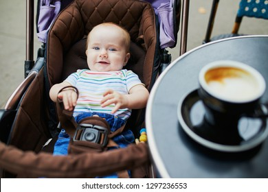 Smiling baby girl in stroller near the table of Parisian outdoor cafe with cup of coffee on it. Going out with kids concept