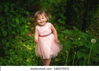 Smiling baby girl walking in the garden