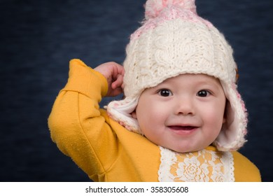 A smiling baby girl wearing a knit winter hat.