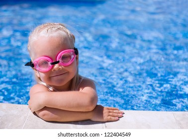 Smiling baby girl  wearing swimming glasses in swimming pool