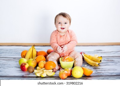 Smiling baby and many kinds of fruit and bowl with yoghurt
