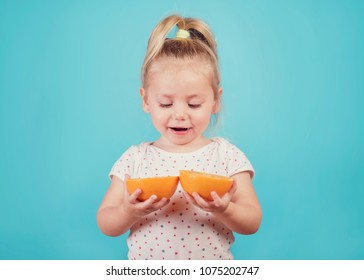 smiling baby with an orange on blue background