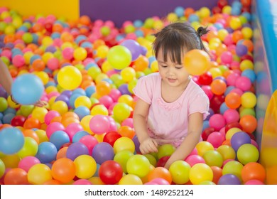 Smiling baby playing in the balls pool. Cute and happy girl. Picture for developmental in children concept.